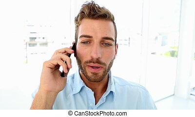 Angry businessman yelling down the phone in his office
