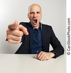 Angry businessman yells and pointing his finger at you
