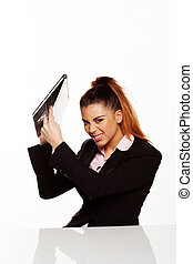 Angry businesswoman about to smash her laptop