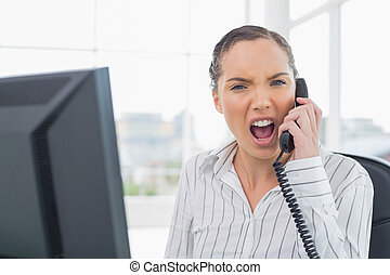 Angry businesswoman screaming on telephone while looking at camera in her office
