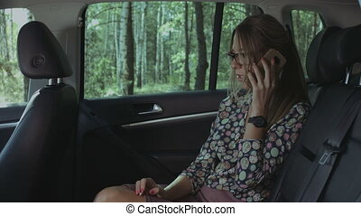 Angry businesswoman talking on cellphone in car