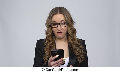 Angry businesswoman texting on her phone on gray background in studio