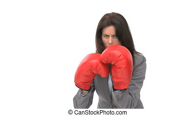 Angry businesswoman with boxing gloves against a white...