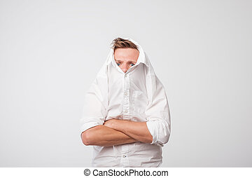 Angry caucasian man pulls a white shirt over his head. loneliness of depressed person.