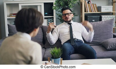 Angry CEO talking to counselor expressing feelings and...