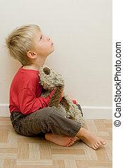 angry child looks upwards holding his toy dog.