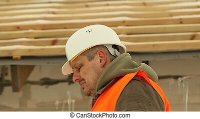 Angry construction foreman talking on the phone