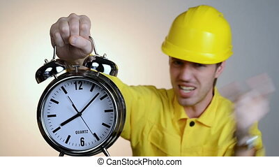 Angry constructor man swearing and showing you alarm clock,...