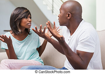 Angry couple having a dispute on sofa at home in the living...