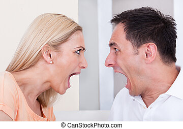 Angry couple shouting at each other - Portrait of angry...