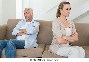 Angry couple sitting on couch not talking to each other at...
