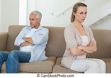 Angry couple sitting on couch not talking to each other