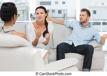 Angry couple talking to their therapist in therapists office