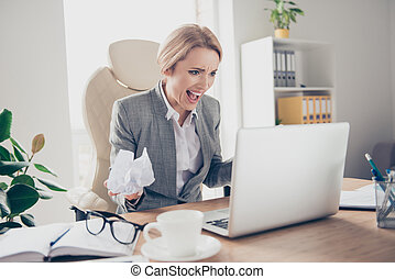 Angry, disappointed, surprised woman in jacket holding crumpled paper in hand, shouting, creaming, looking at laptop, sitting on armchair at her desktop