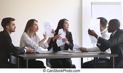 Angry diverse team colleagues argue over paperwork during...
