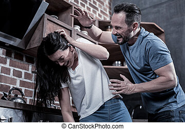 Angry drunk man beating his wife