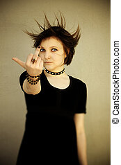 Angry emo - brunette girl showing middle finger, toned photo...
