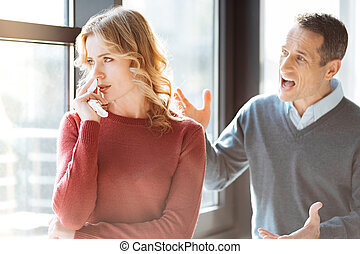 Angry emotional man shouting at his wife
