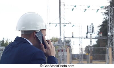 angry engineer screaming, talking on the phone against a power plant background