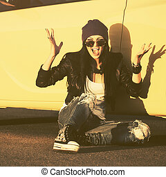 Angry fashion hipster woman sitting on sidewalk next to her car