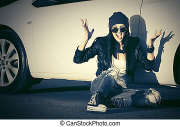 Angry fashion punk woman sitting next to her car