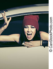 Angry fashion woman shouting in a car