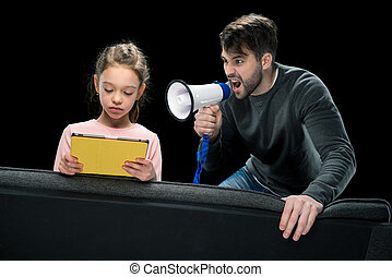 Angry father with megaphone screaming at upset daughter using digital tablet, family problems concept