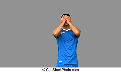 Angry football player holding his head on grey screen in...