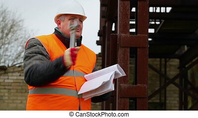 Angry foreman with documents and adjustable wrench in...