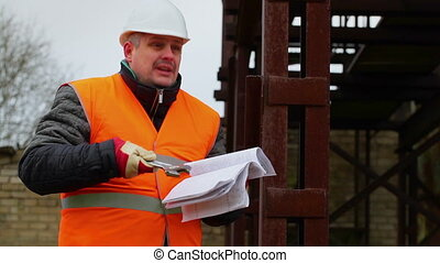Angry foreman with documents and adjustable wrench