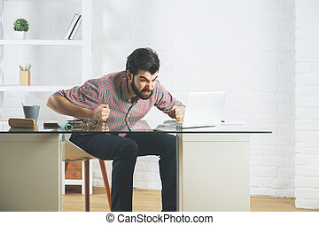 Angry furious businessman using laptop