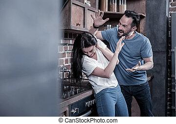 Angry furious man raising his arm