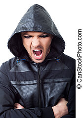 Young male gangster with black hood looking at camera screaming hands on chest