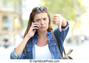 Angry girl talking on phone with thumbs down