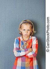Angry Girl With Arms Crossed Against Blue Wall