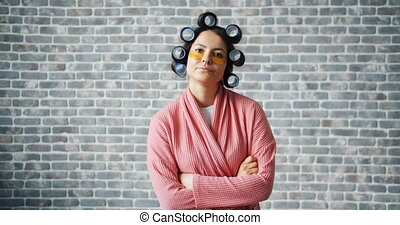 Angry girl with hair curlers and eye patches standing with...