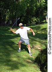 Angry Golfer - An angry golfer about to throw his club in...