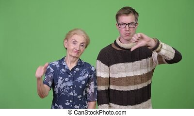 Angry grandmother and grandson giving thumbs down together