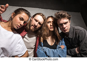 Picture of young angry hipsters friends standing over gray background looking camera.