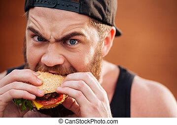 Angry irritated young man eating hamburger outdoors - Angry ...