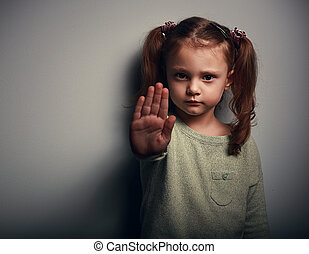 Angry kid girl showing hand signaling to stop useful to...