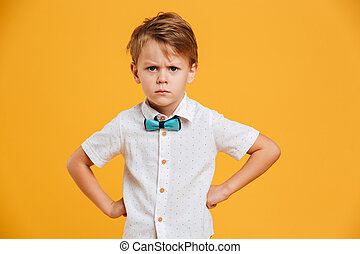 Angry little boy child standing isolated