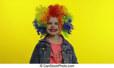 Angry little child girl clown in colorful wig making evil ...