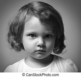 Angry little kid girl portrait looking. Black and white...