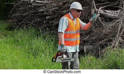 Angry Lumberjack with chainsaw talking near the pile of...