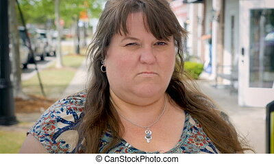 """Angry, mad, and bothered obese woman standing outside..."