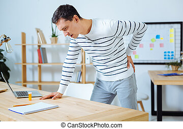 Angry male person keeping his back bent