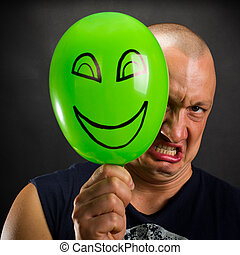 Angry man hiding behind happy balloon