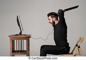 Angry man is destroying a keyboard and monitor of computer on gray background