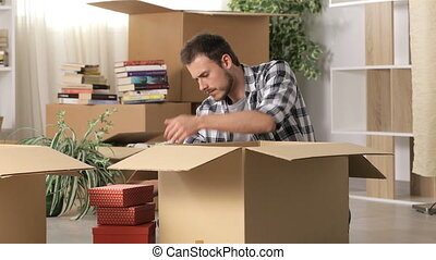 Angry man moving home after divorce boxing belongings and...